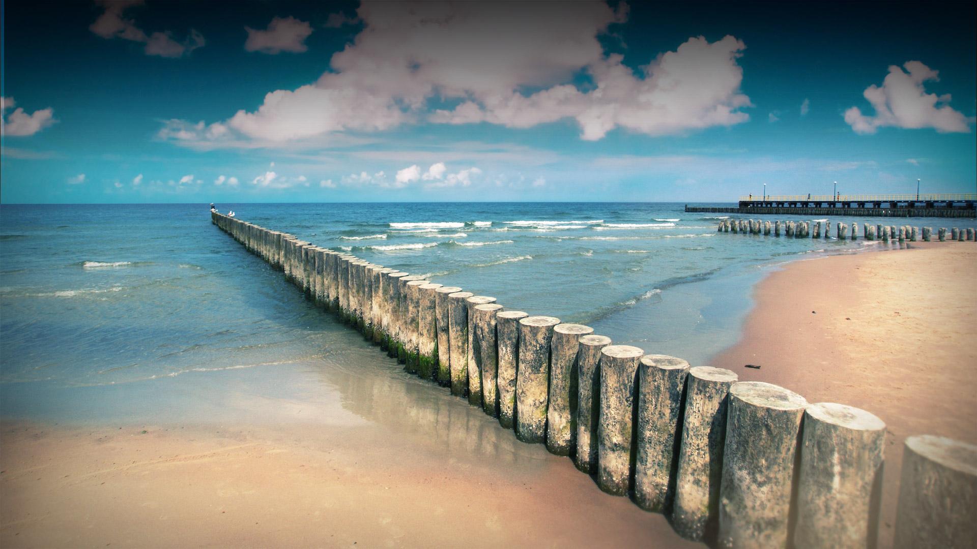 Spokojna woda, falochrony wchodzące w morze. W oddali widoczne molo.